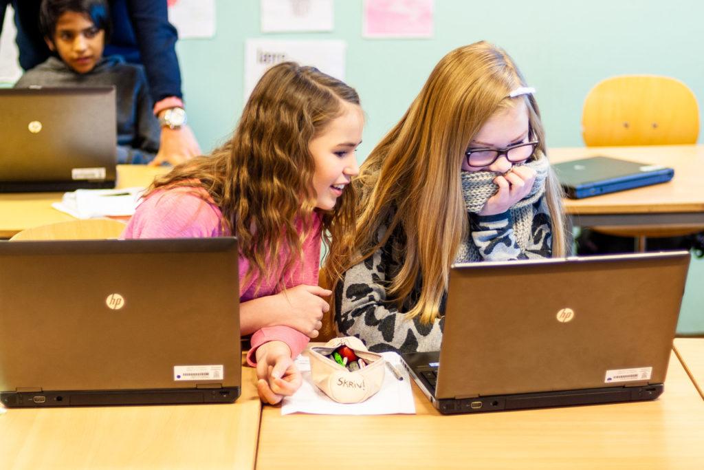 To ungdomsskolejenter diskuterer noe på en PC