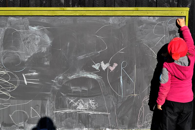 Barn som skriver på tavle ute