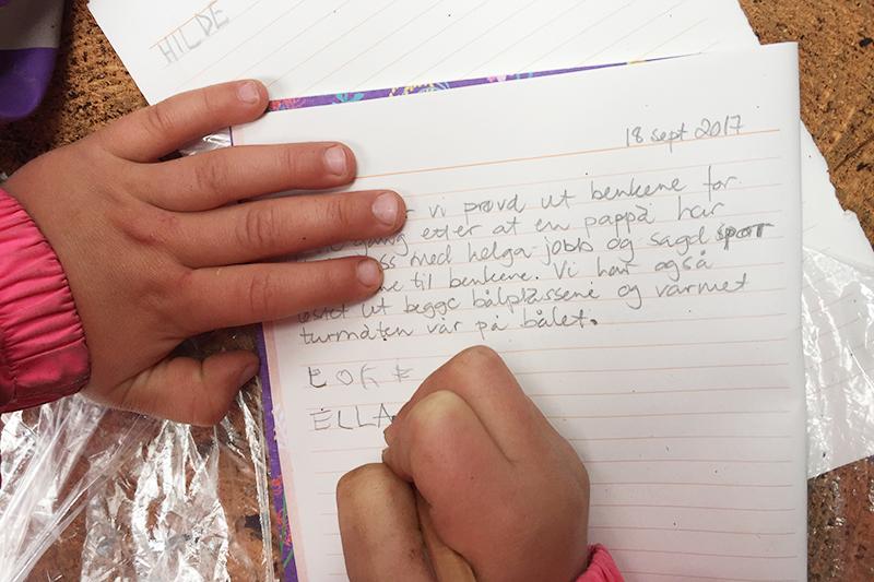 Barnehender som skriver i kladdebok