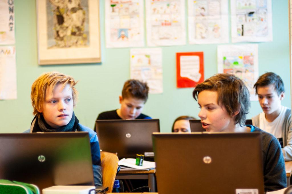To ungdomsskolegutter jobber på PC