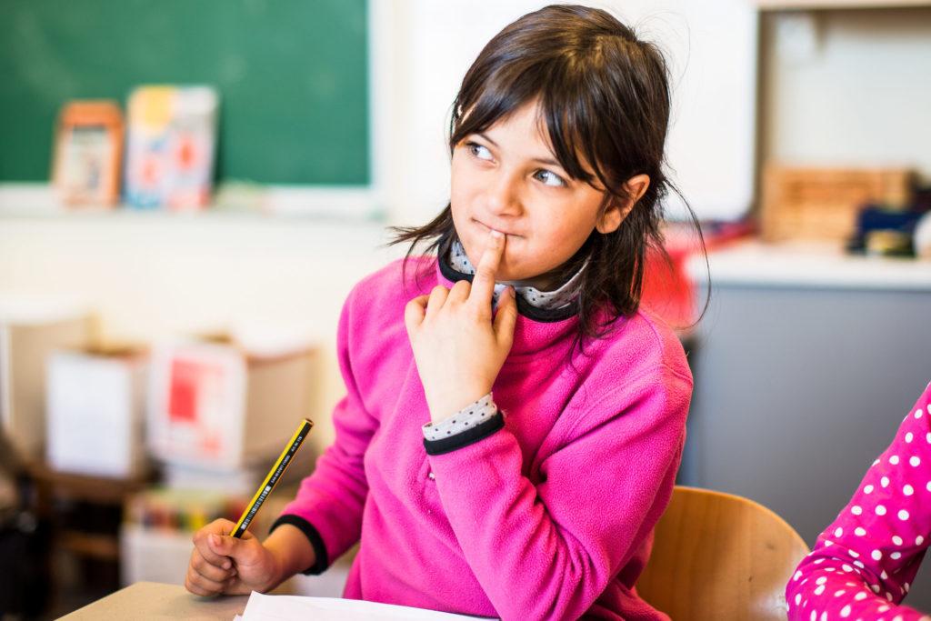 Barneskolejente som tenker seg om og skriver.
