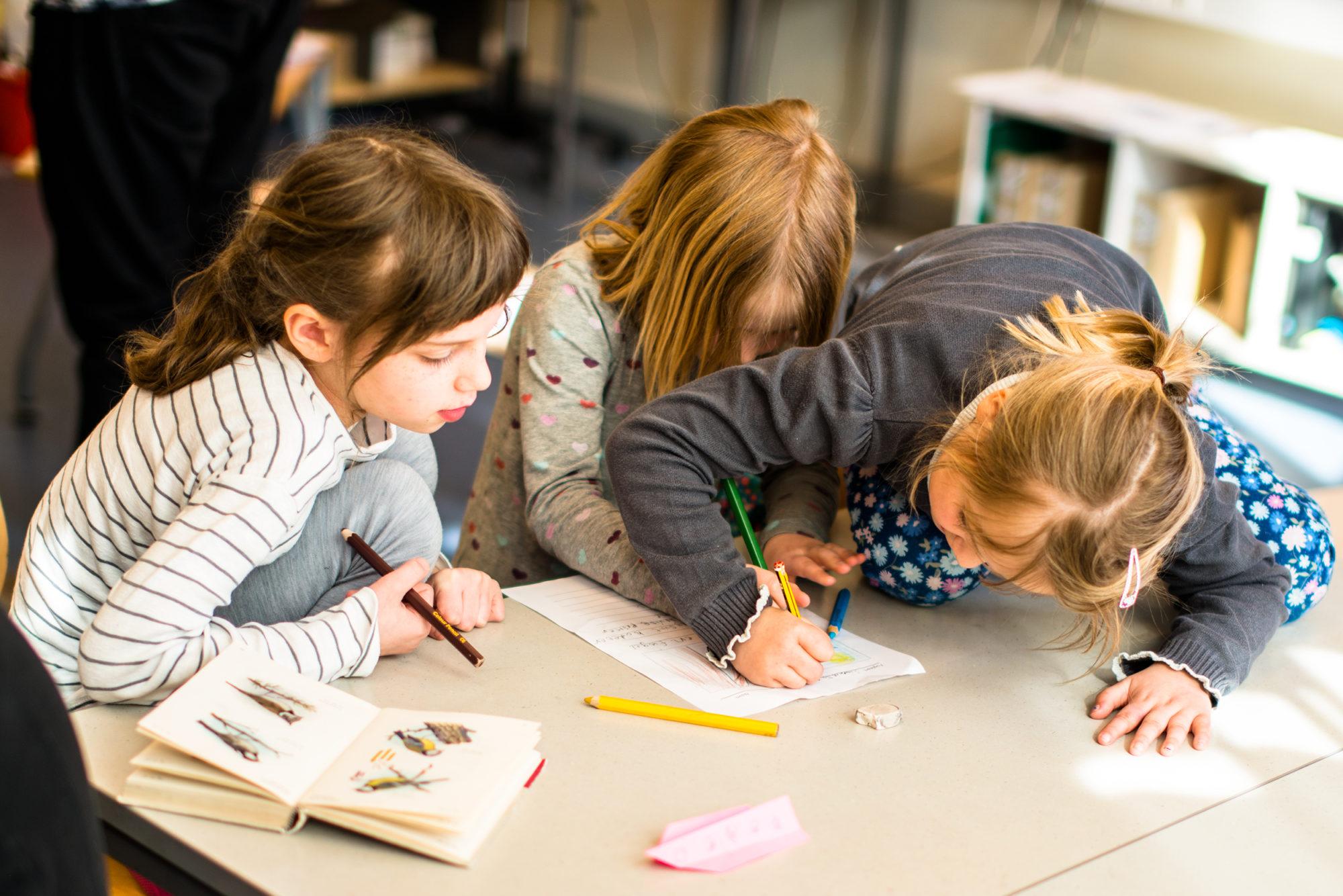 Tre barneskolejenter samskriver