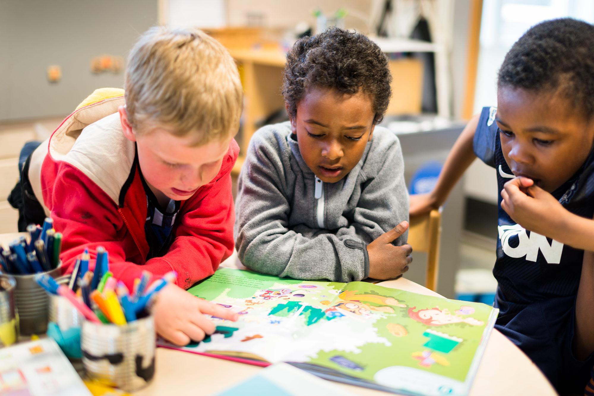 Barn som sitter rundt et bord med bok
