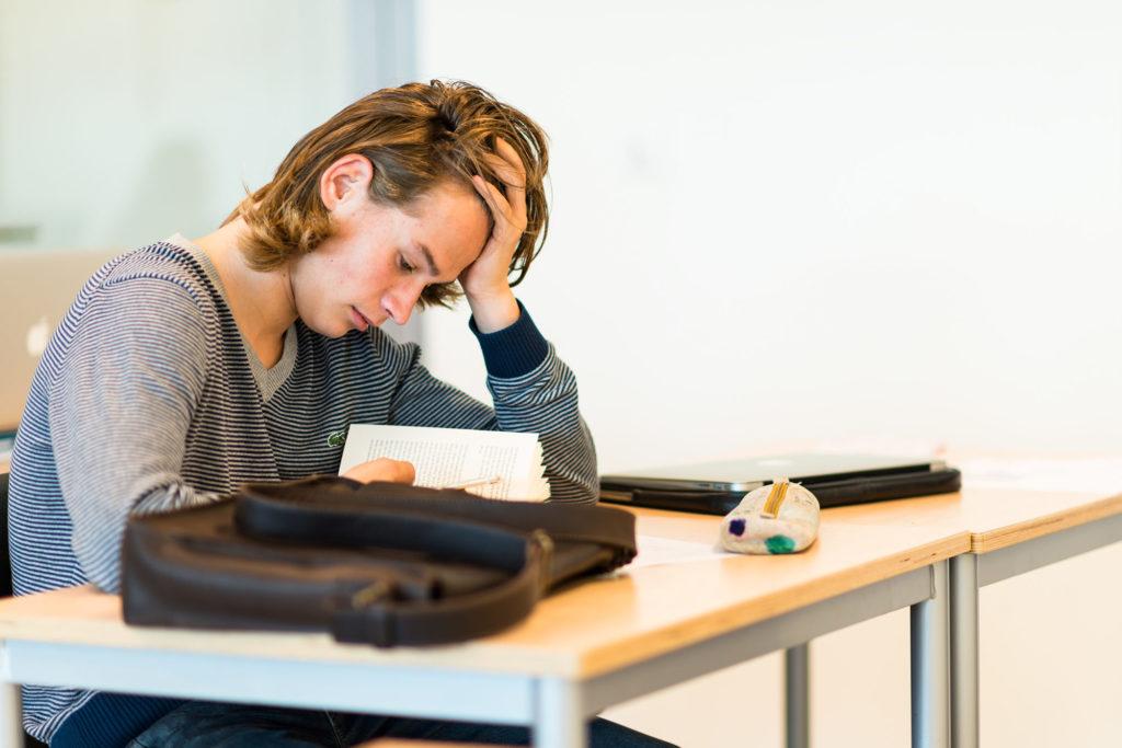 Gutt på vgs som sitter ved pult og leser
