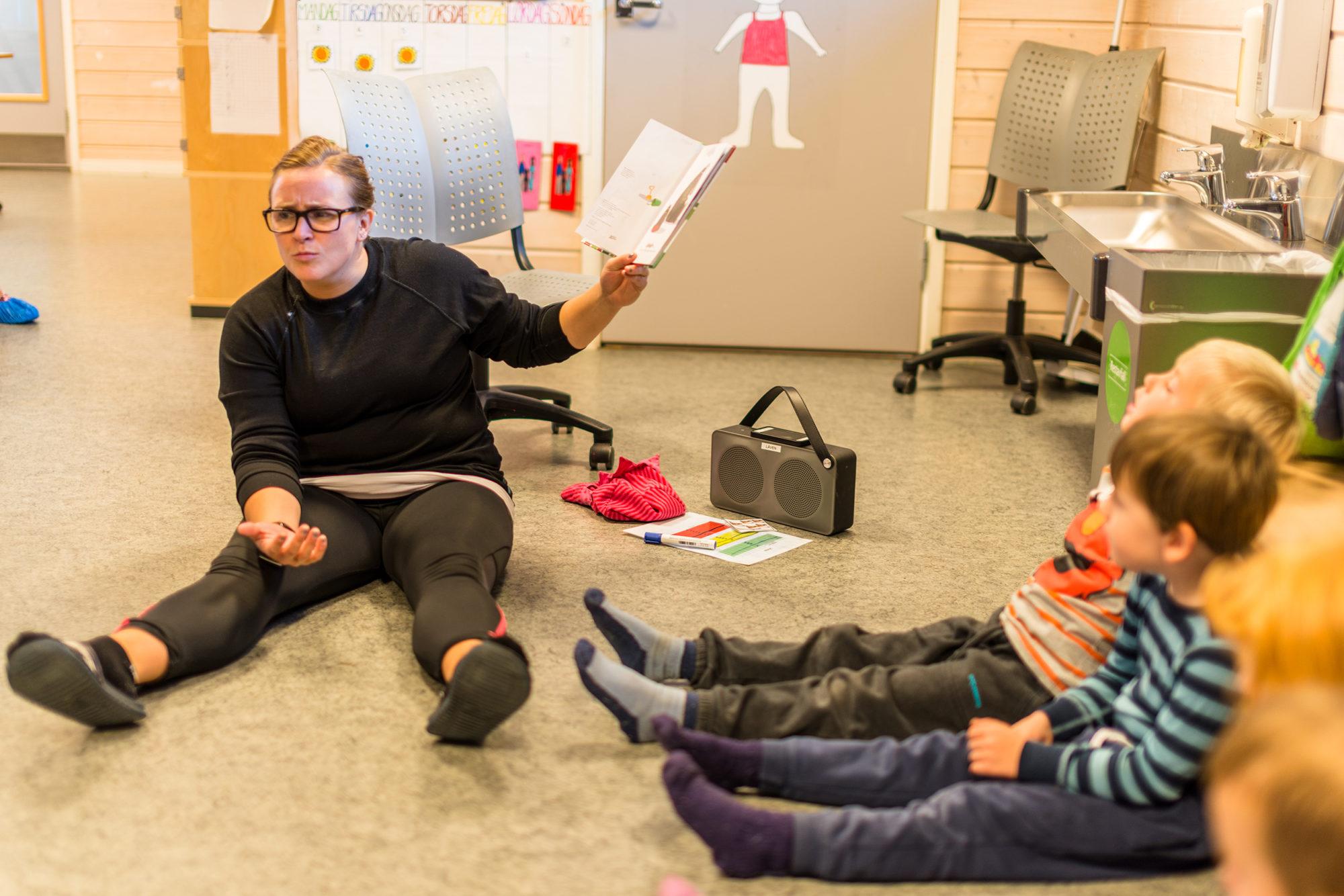 Voksen i barnehage har lesestund med barna