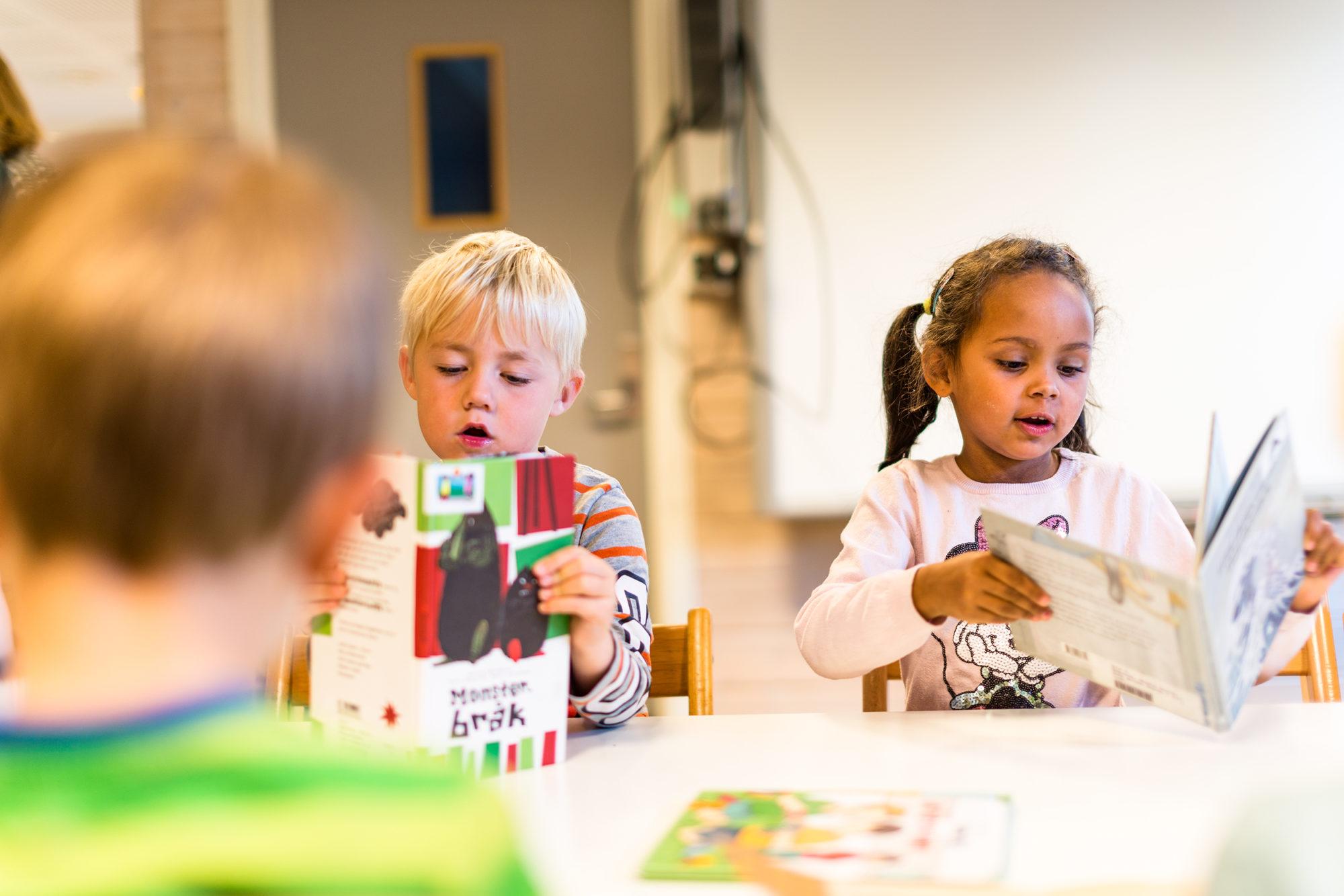 To barnehagebarn som leser i bøker