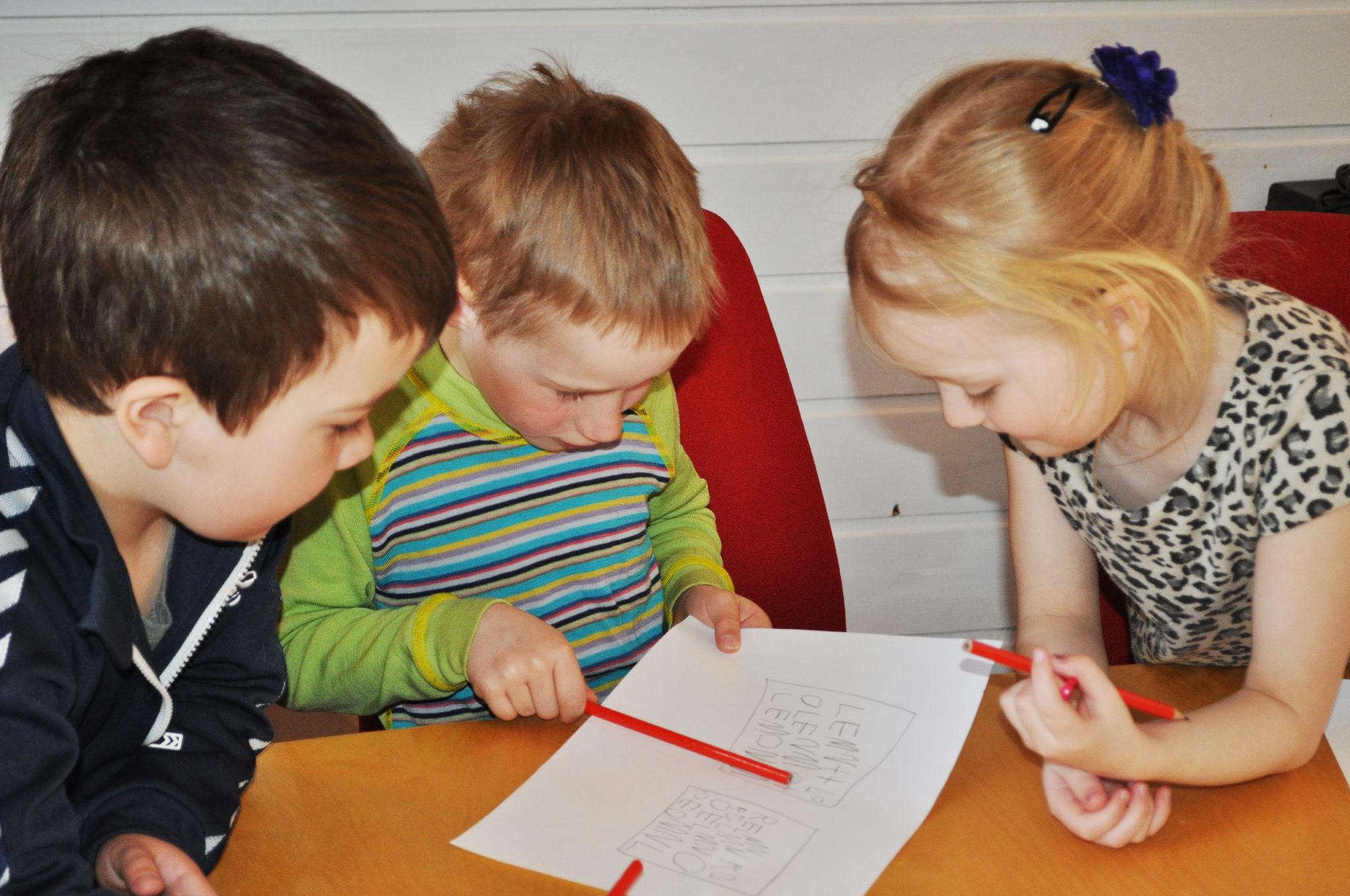 Barnehagebarn som sitter rundt et bord og skriver