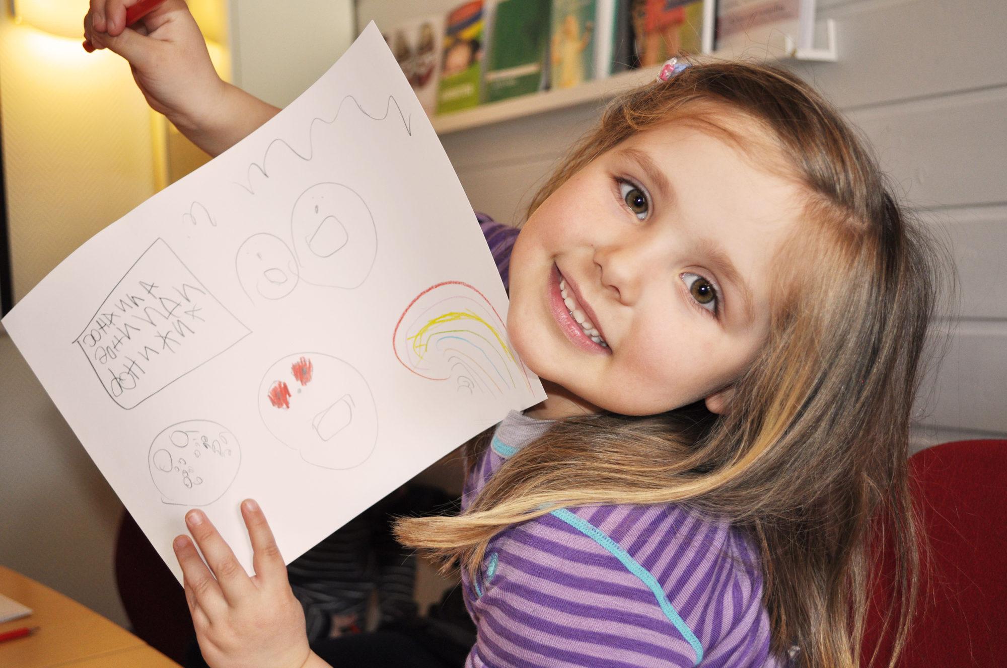 Barnehagebarn som viser frem teksten sin