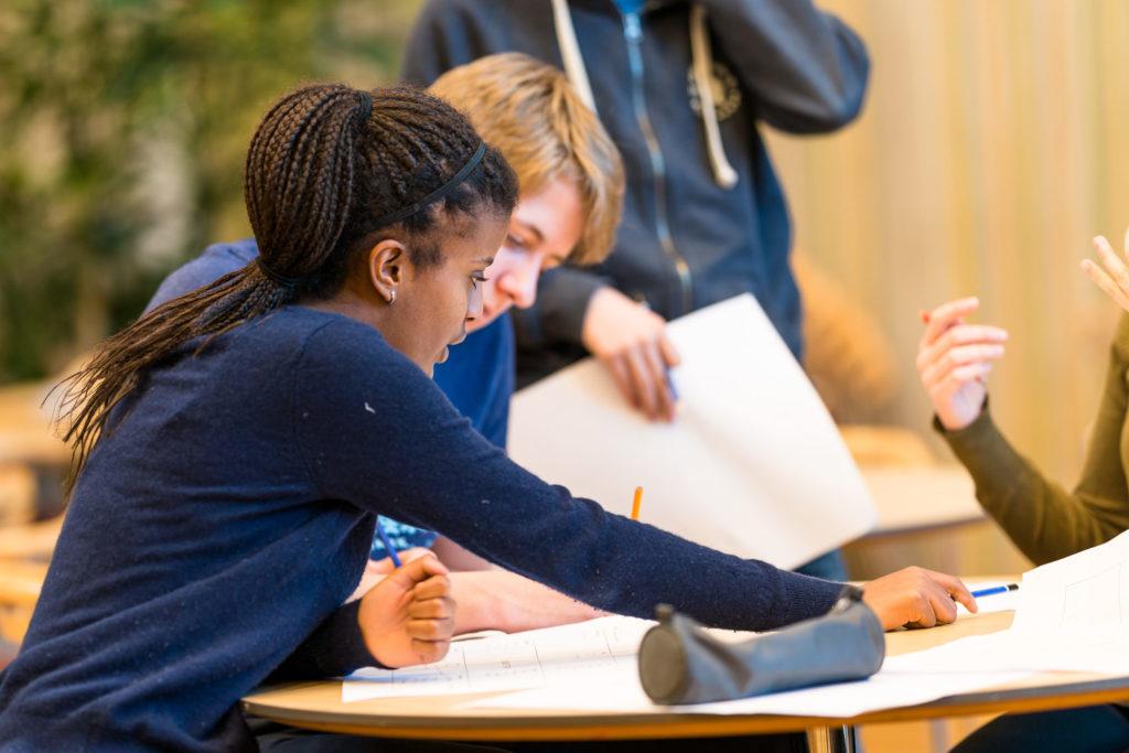 Ungdomsskoleelever diskuterer rundt et bord
