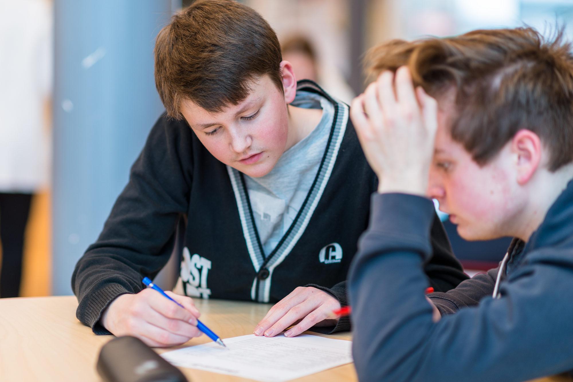 To ungdomskoleelever rundt et bord