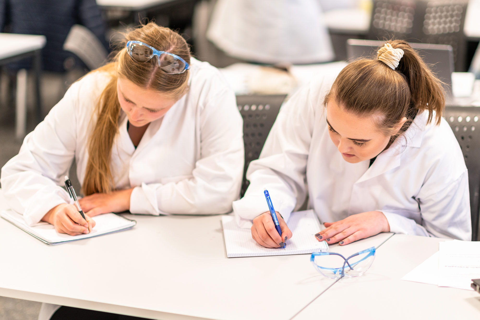 To studenter som skriver for hånd på lab