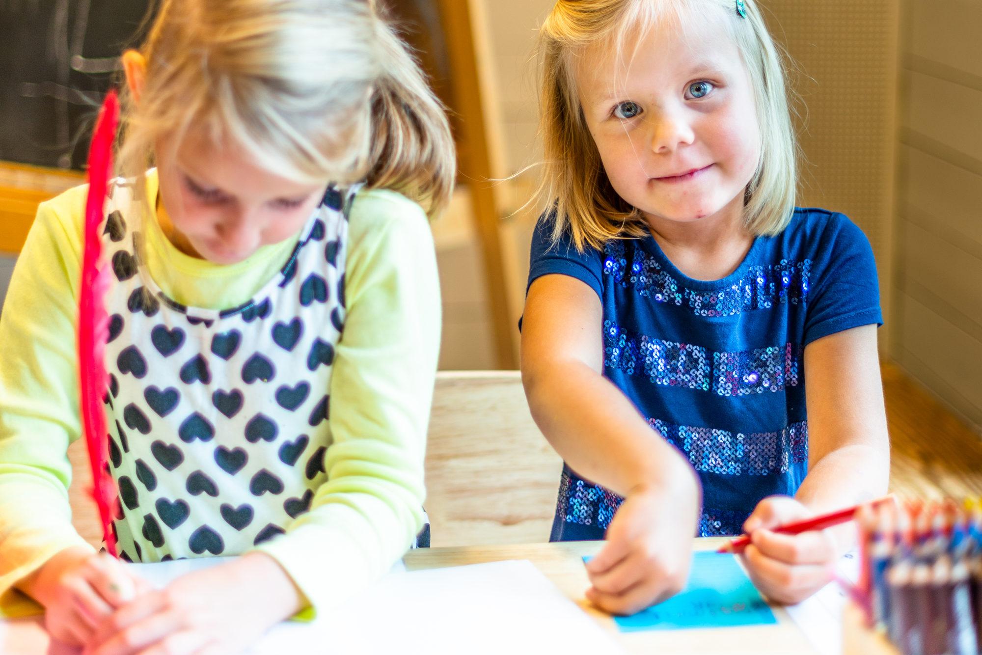 To barnehagejenter som sitter og skriver / tegner