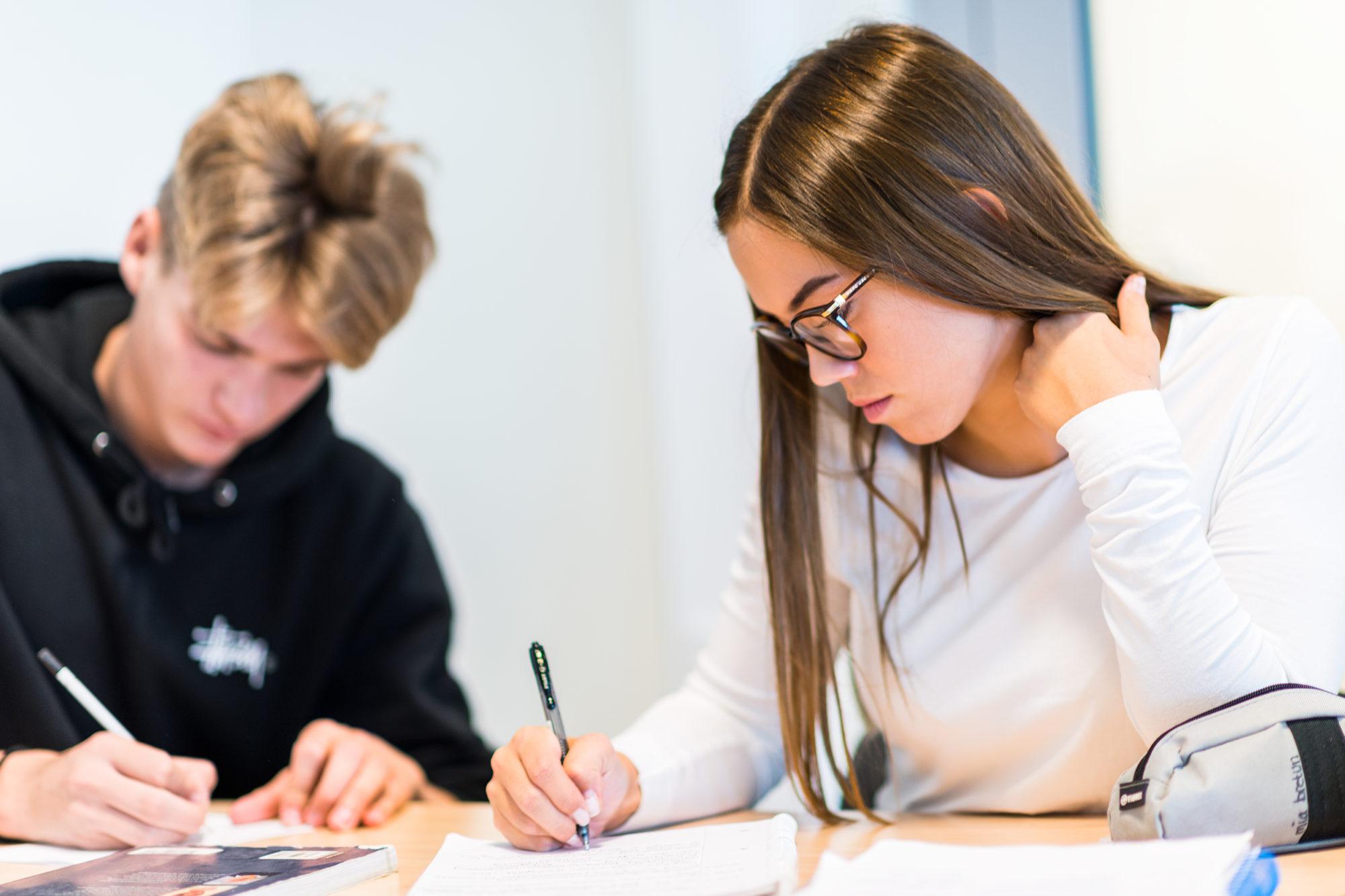 Gutt og jente på vgs som skriver for hånd