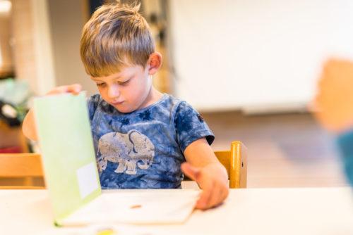 Barnehagegutt som leser i bok