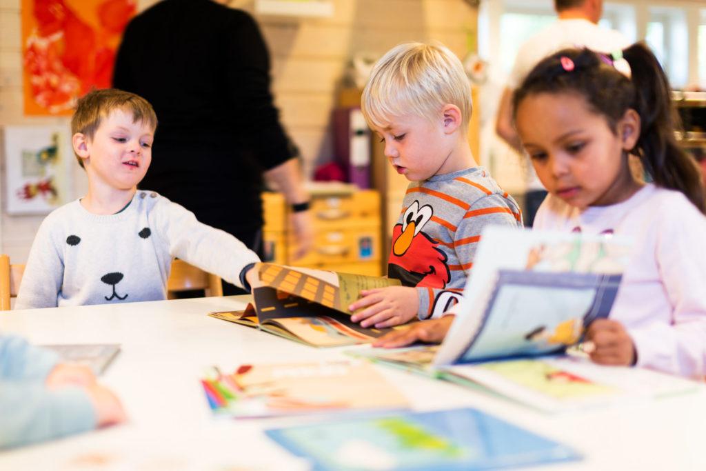 Barnehagebarn som leser i bøker