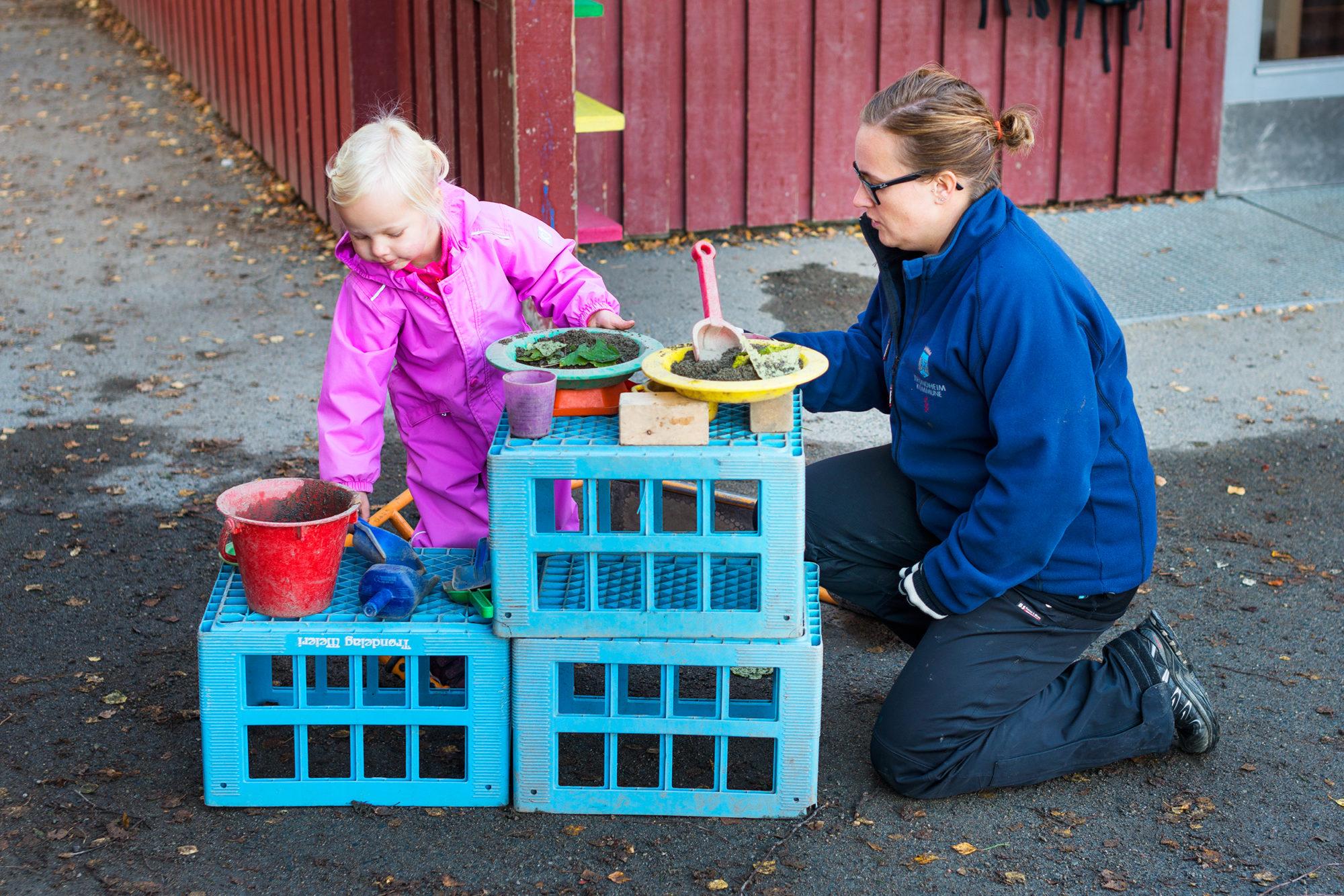 Voksen og barnehagejente leker kjøkken ute