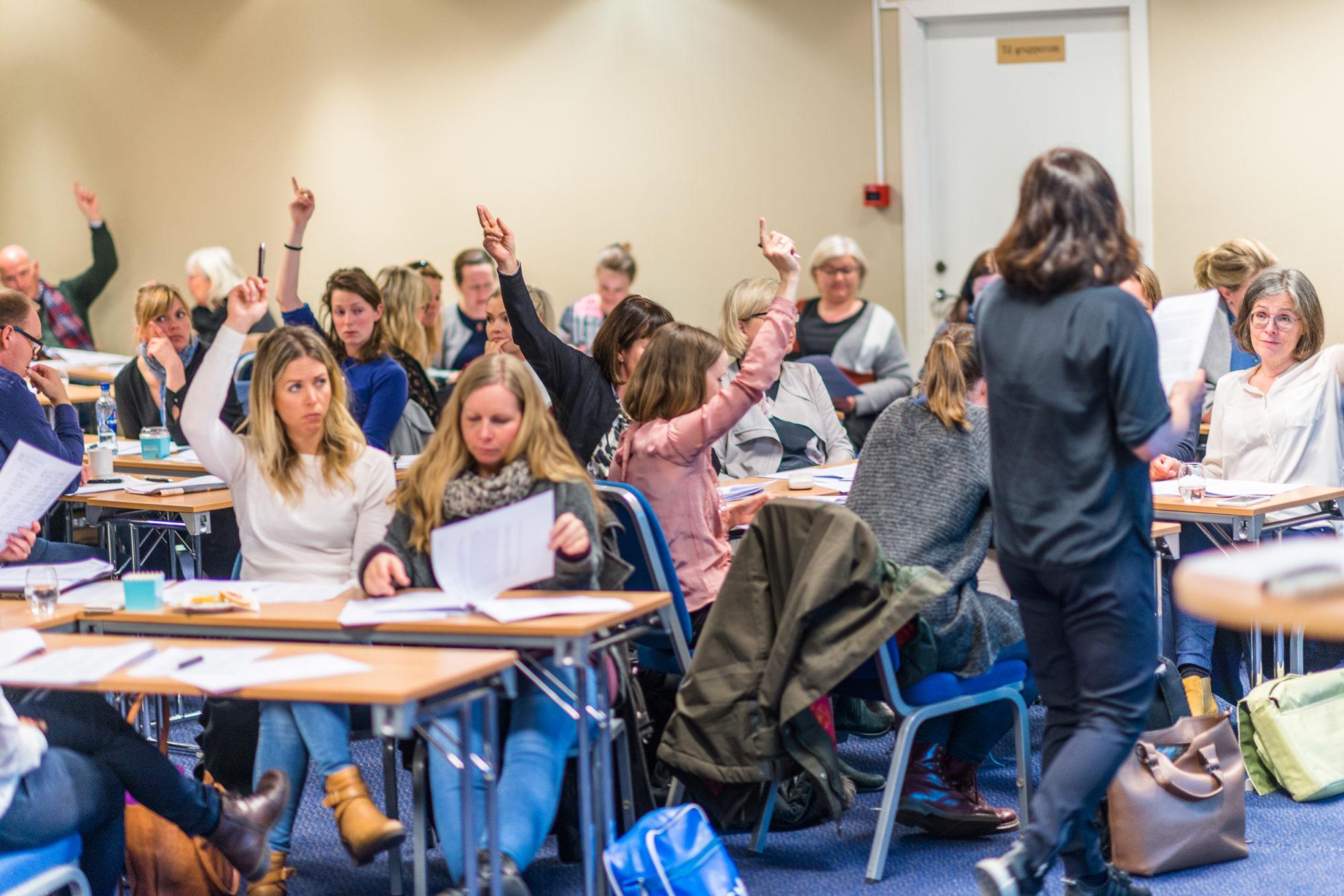Lærere som rekker opp handa i klasserom