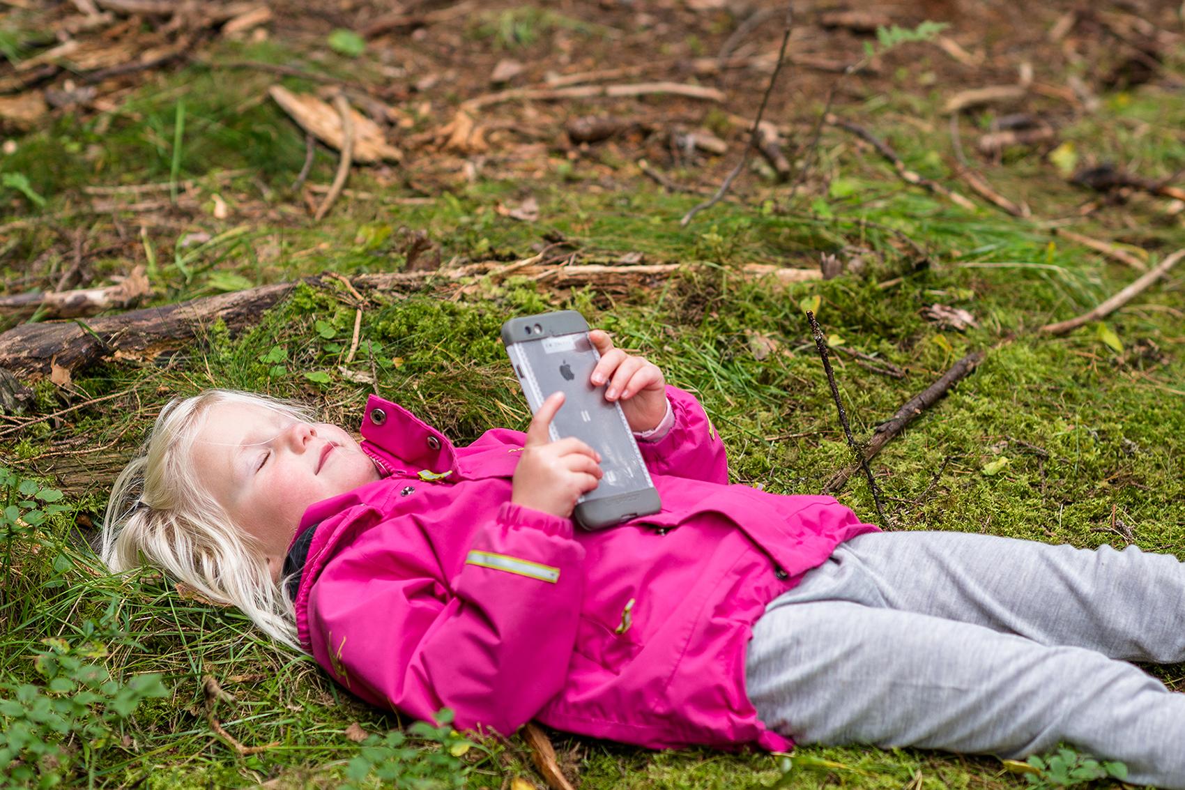 Barnehagebarn som undrer seg med mobiltelefon