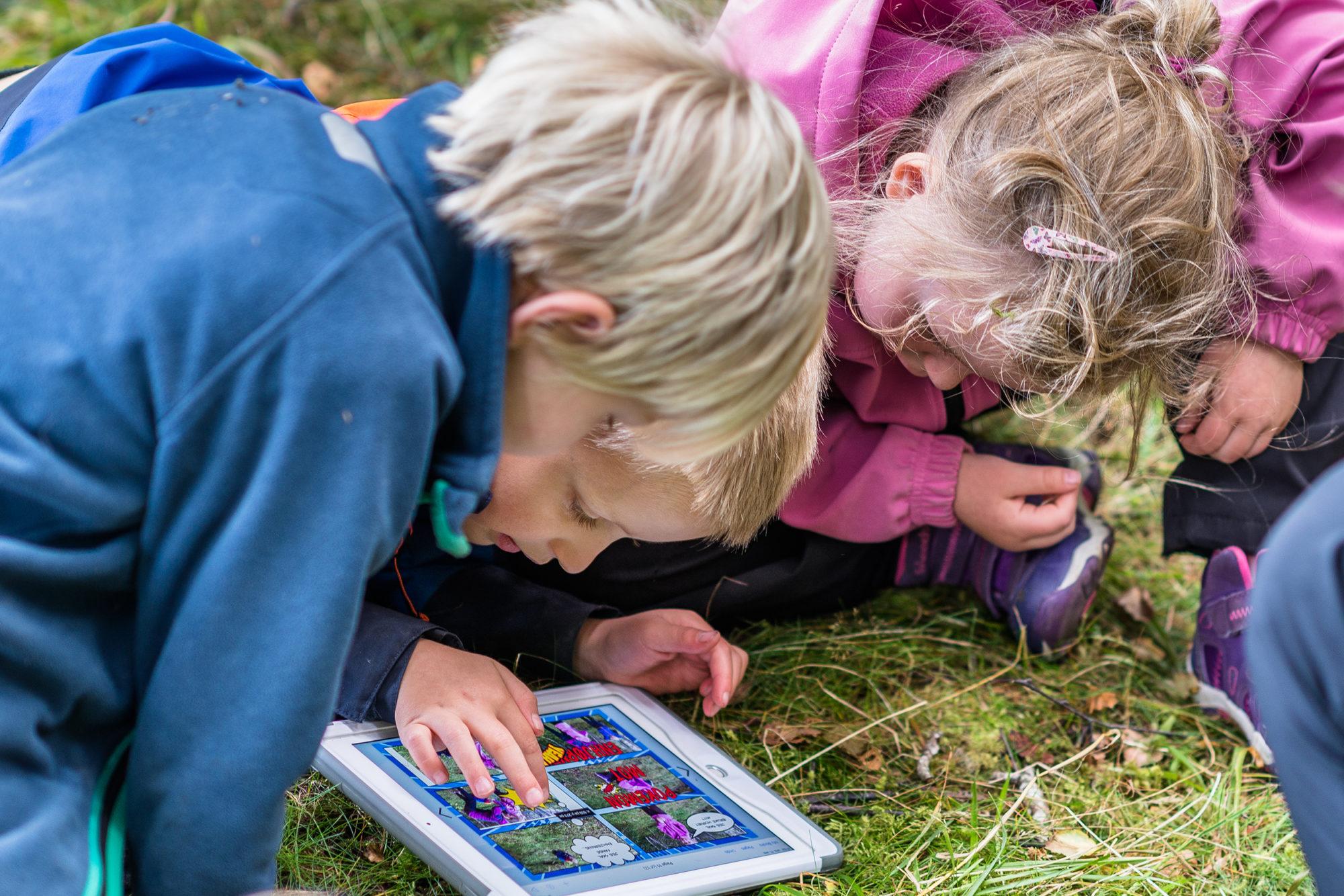 Barnehagebarn som lager digital bildebok ute i baturen