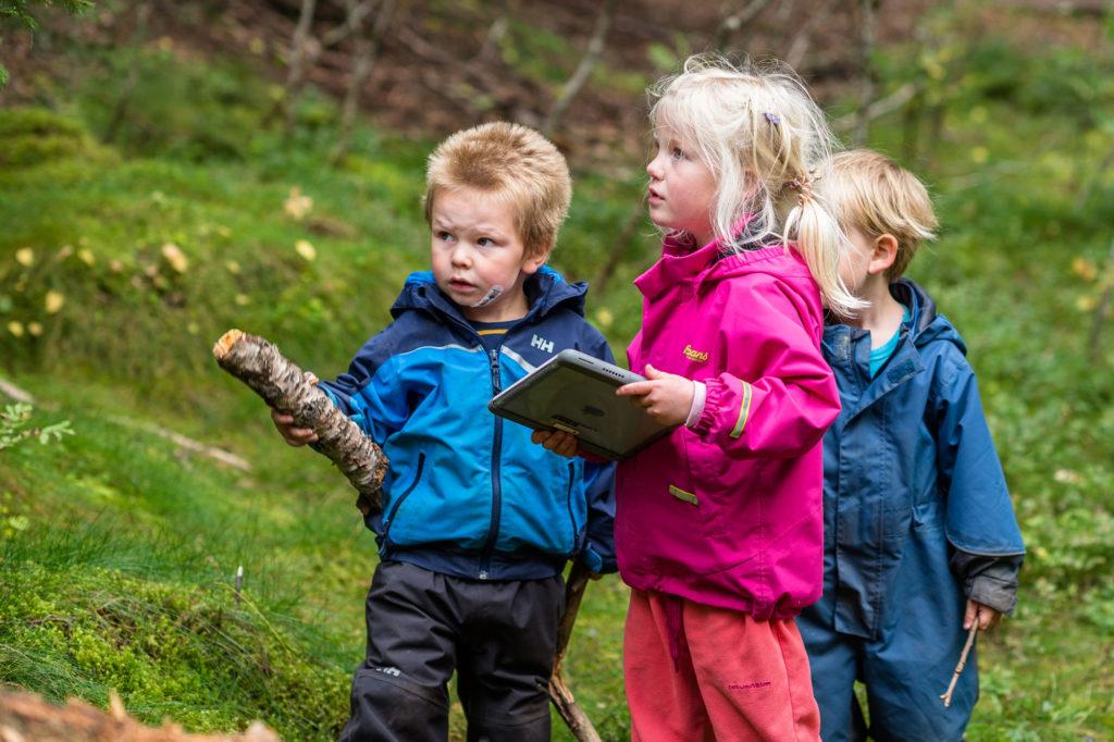 Barnehagebarn ute i naturen med iPad og pinner