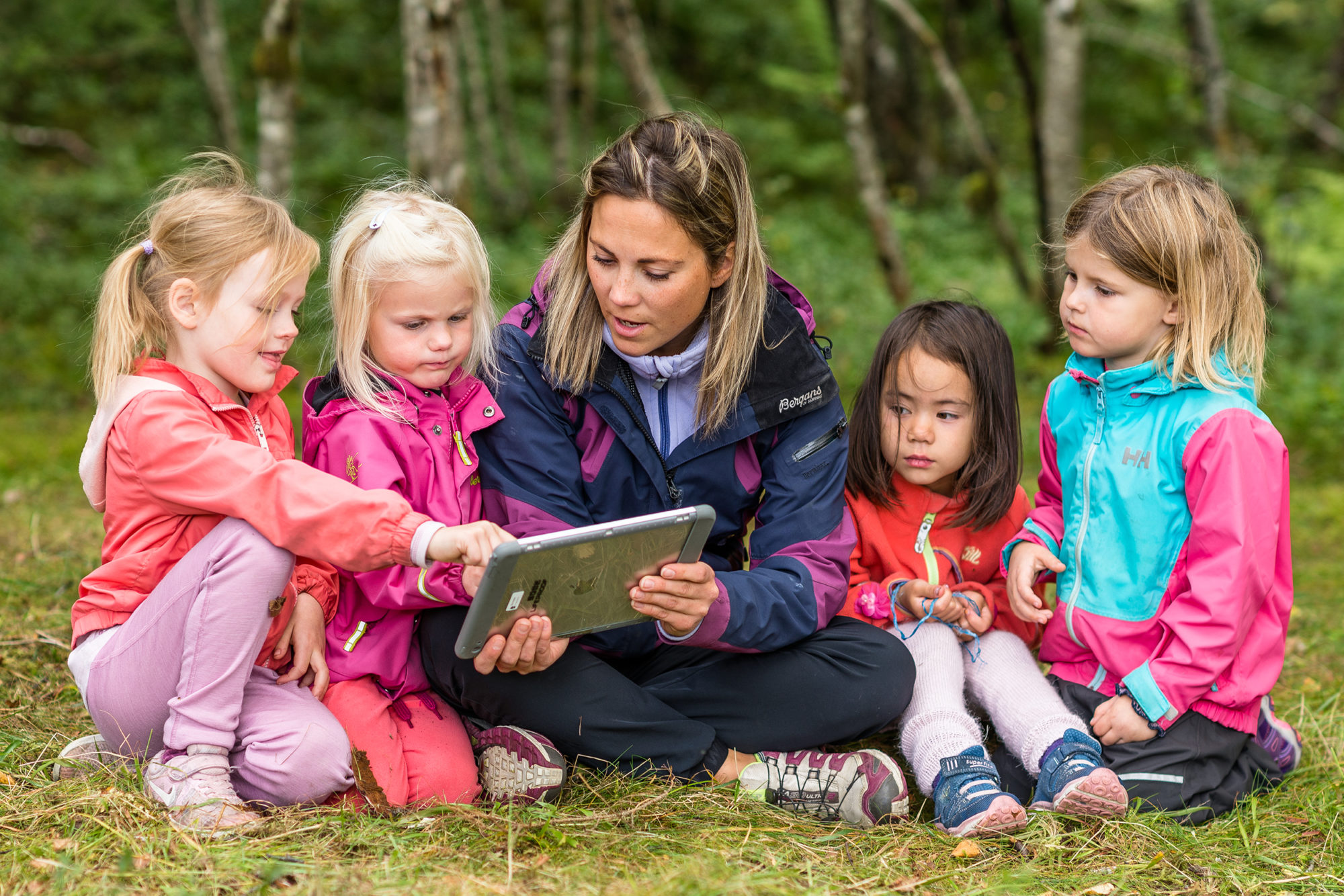En voksen og fire barnehagebarn i naturen med iPad
