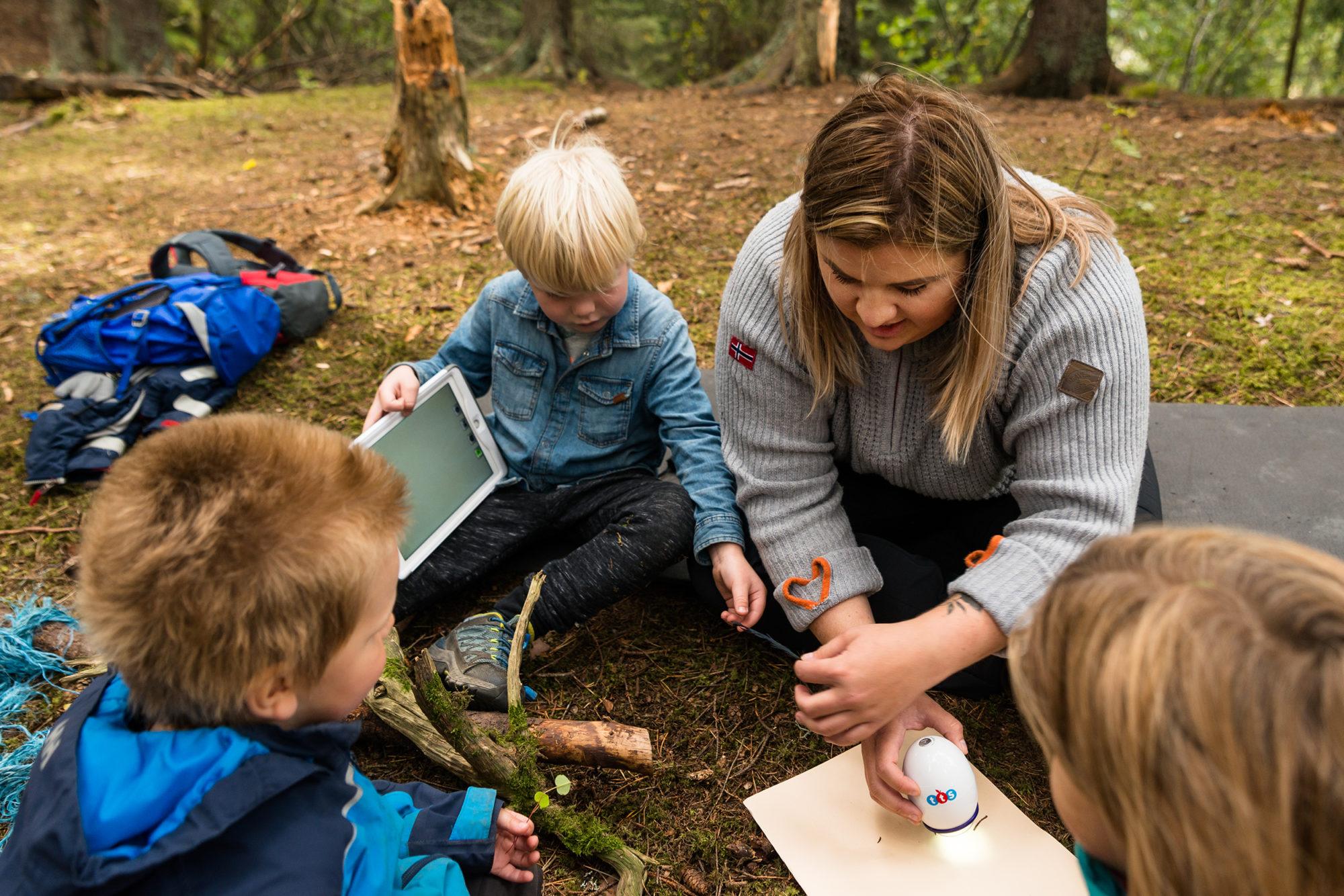 Voksen og barnehagebarn gjør undersøkelser i naturen med digitale hjelpemiddel