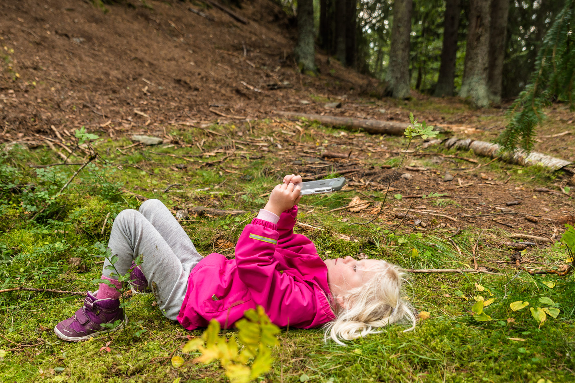 Barnehagebarn ligger i gresset og ser på iPhone