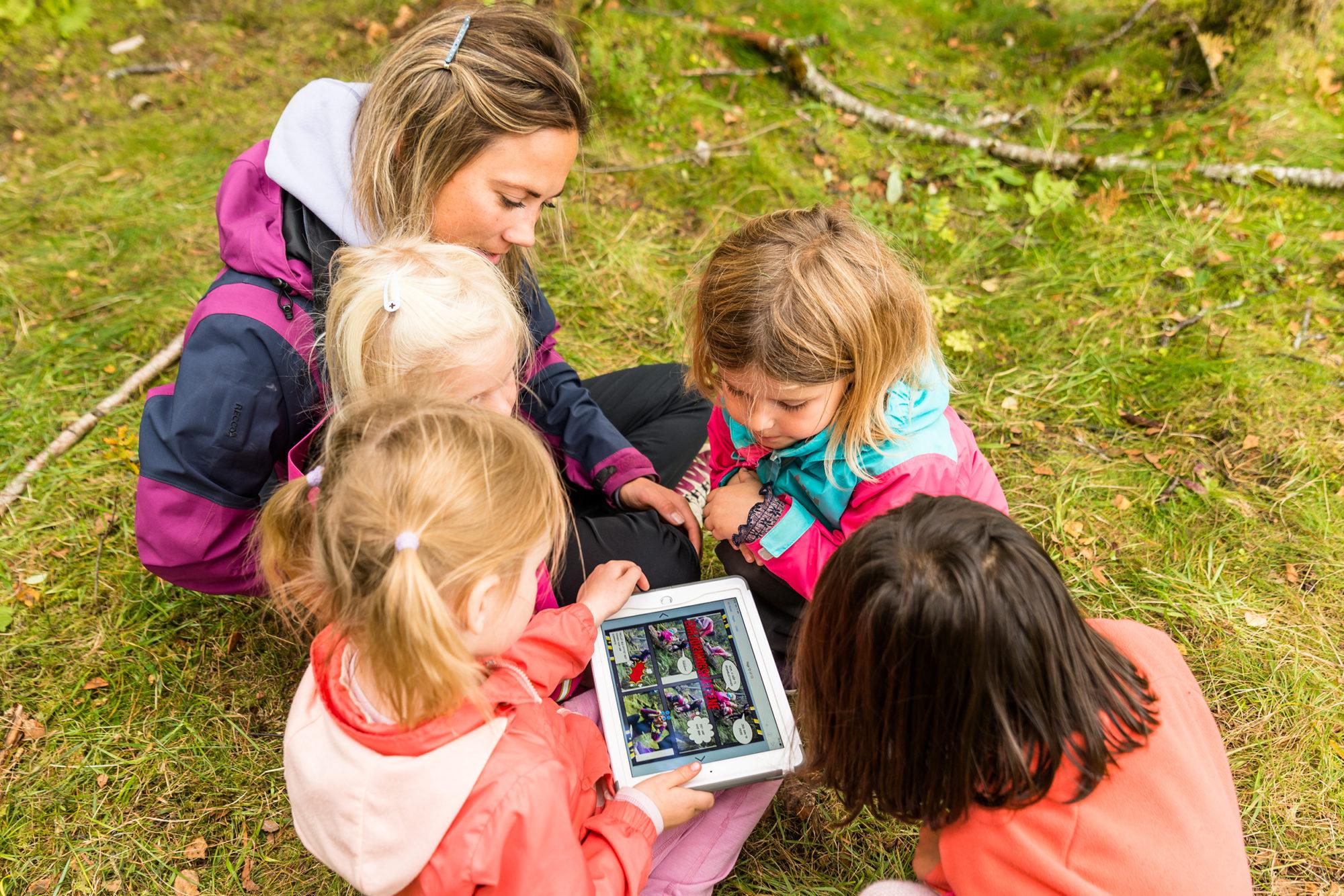 Barnehagebarn lager digital bok mens de er ute i naturen