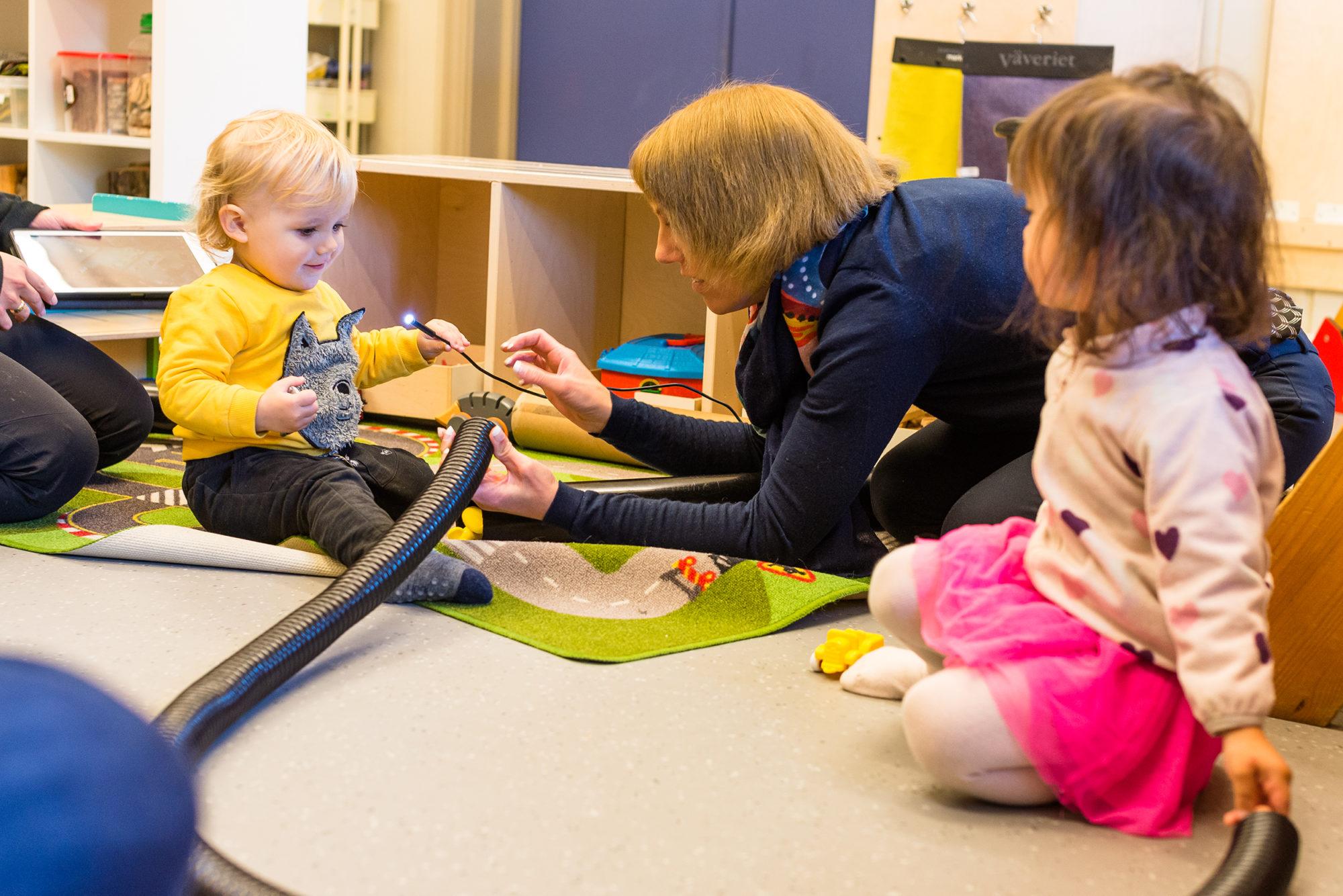 Voksen og barnehagebarn utfosker med trådløst mikroskop