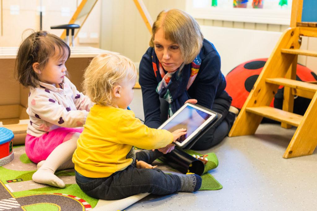 Barnehagebarn og voksen med iPad