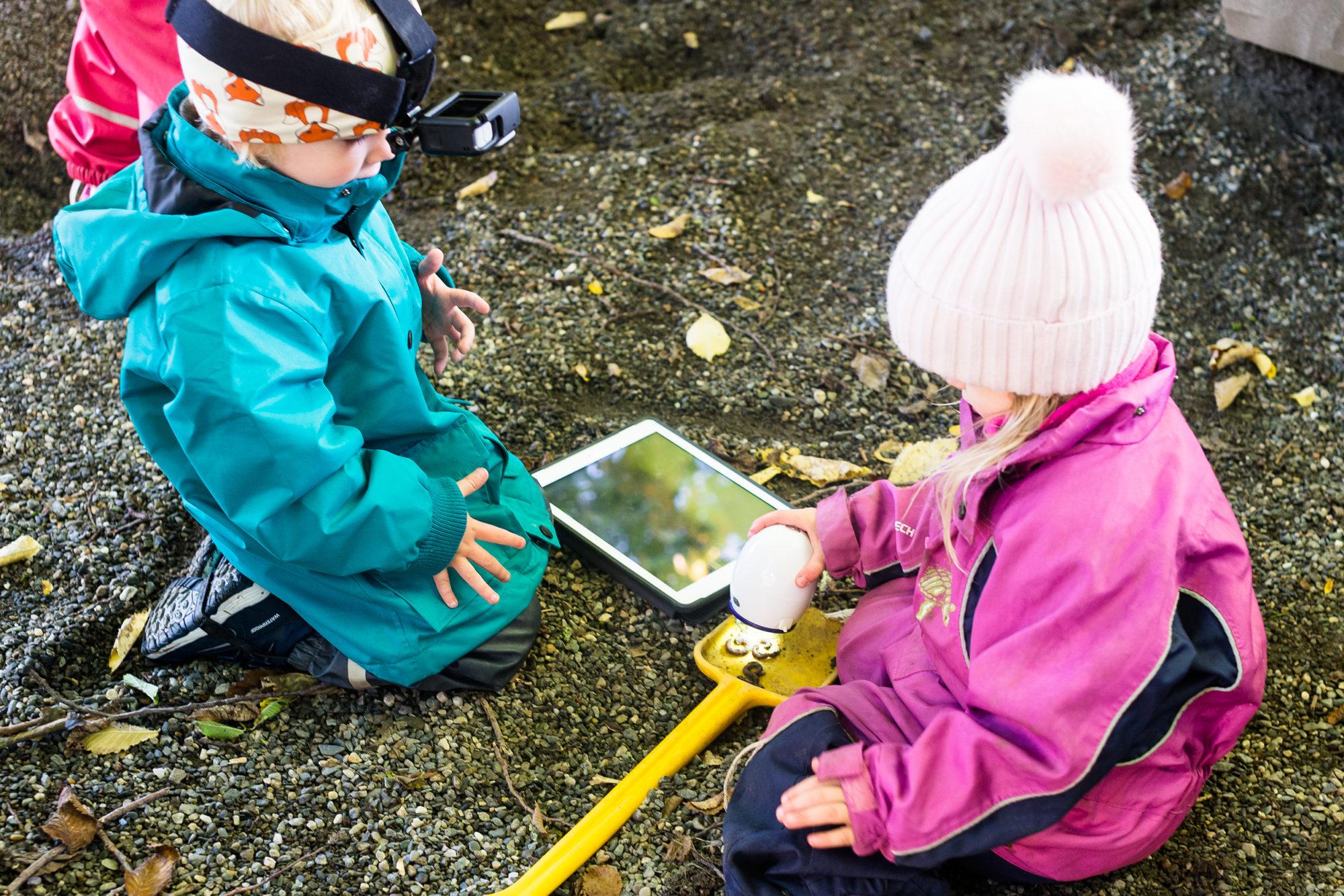 Barnehagebarn i sandkasse med GoPro, iPad og digitalt mikroskop