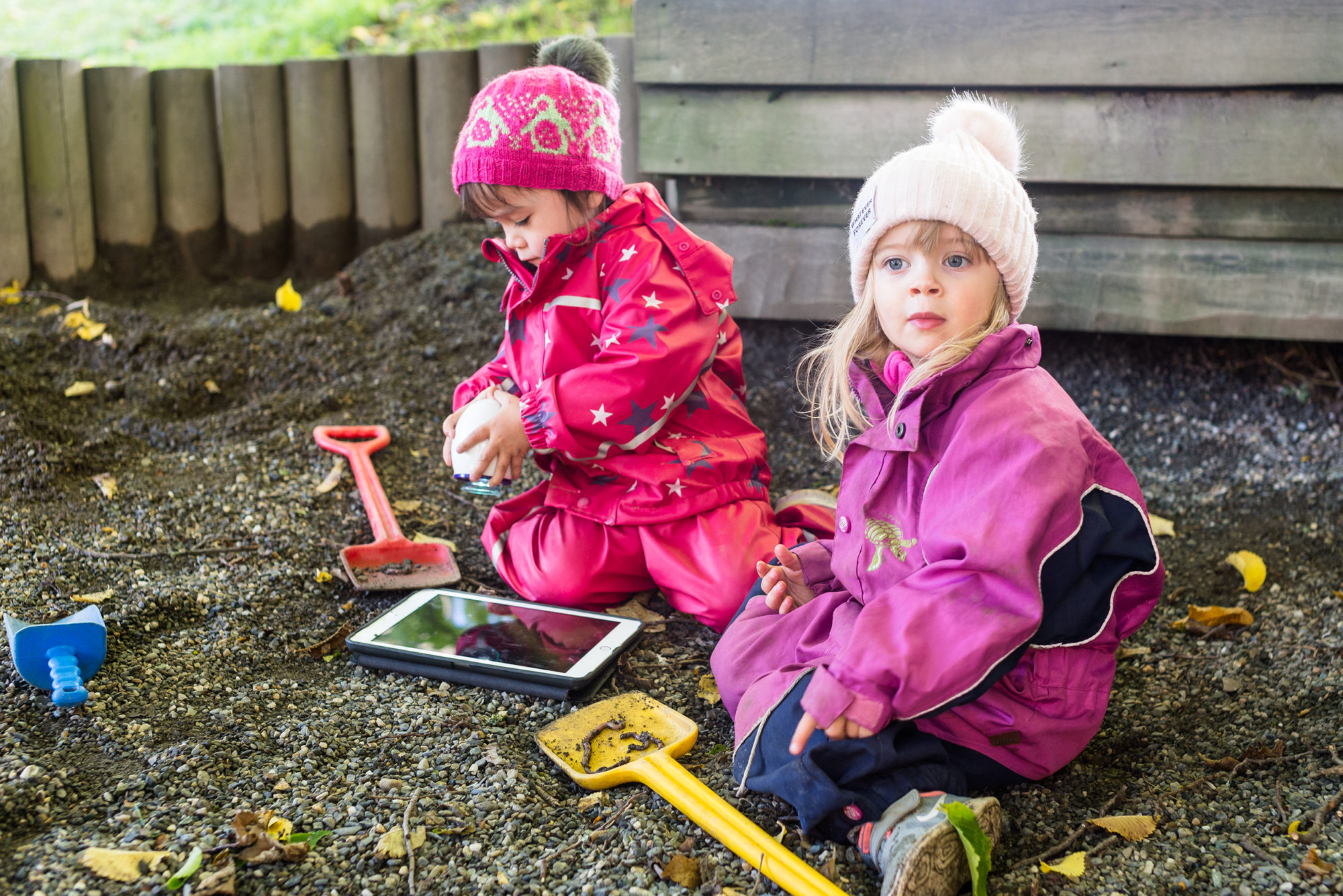 To barnehagebarn undersøker mark med digitalt utstyr
