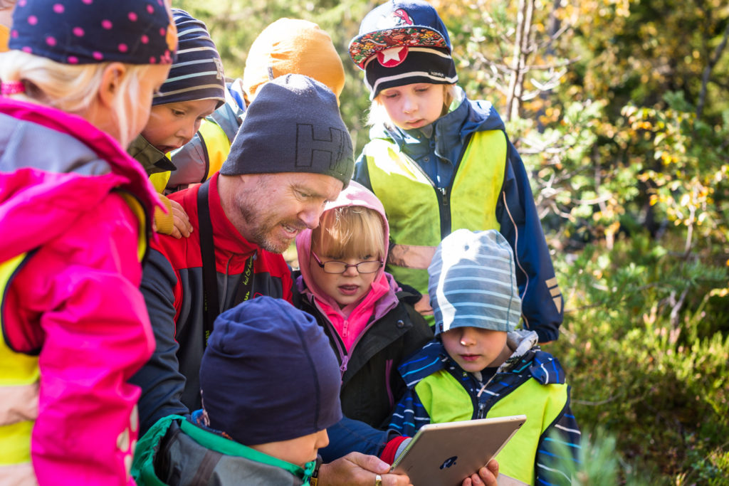 Voksen og barnehagebarn med iPad i naturen
