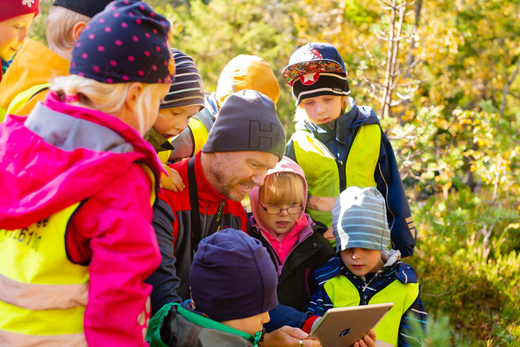 Barnehagebarn og en voksen ser på iPad i skogen