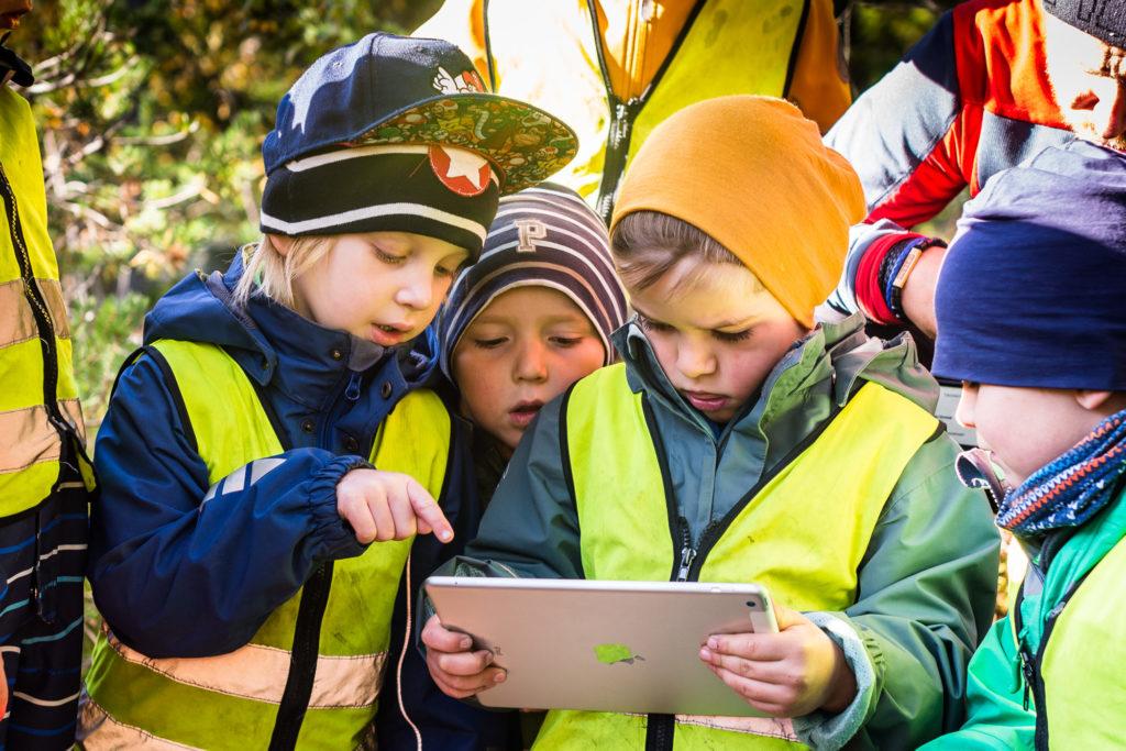 Barnehagebarn studerer i iPad ute i naturen