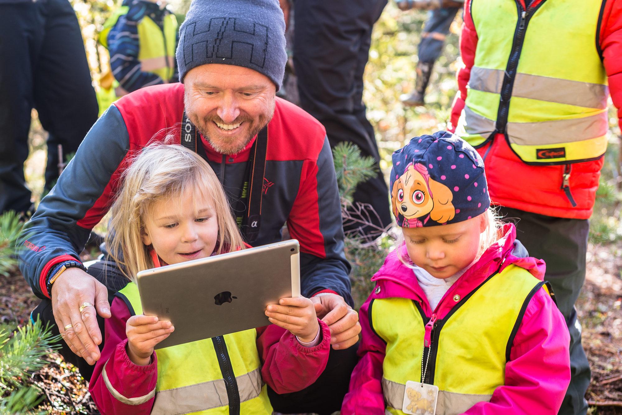 Barnehagelærer og barnehagebarn i naturen med iPad