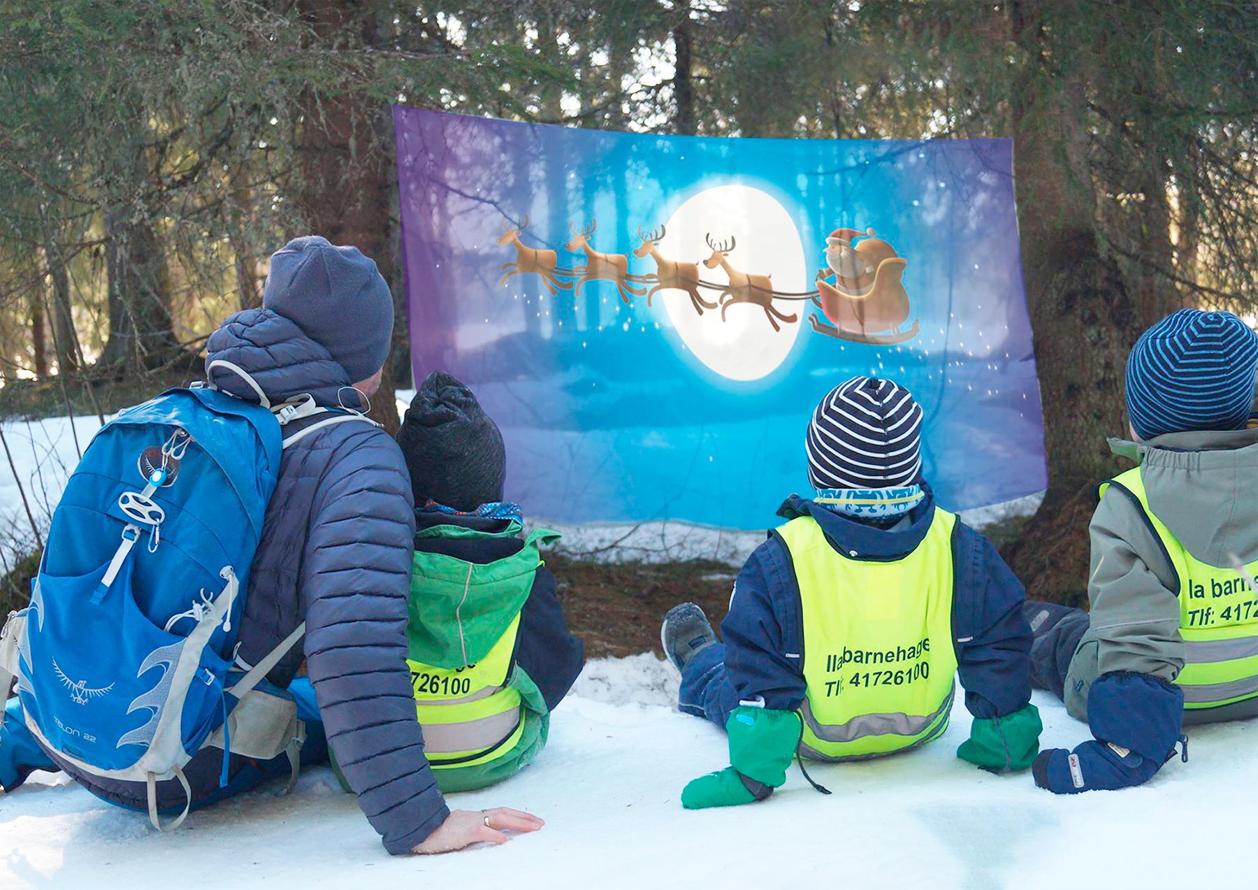 Barnehagebarn ser på film med prosjektor i skogen