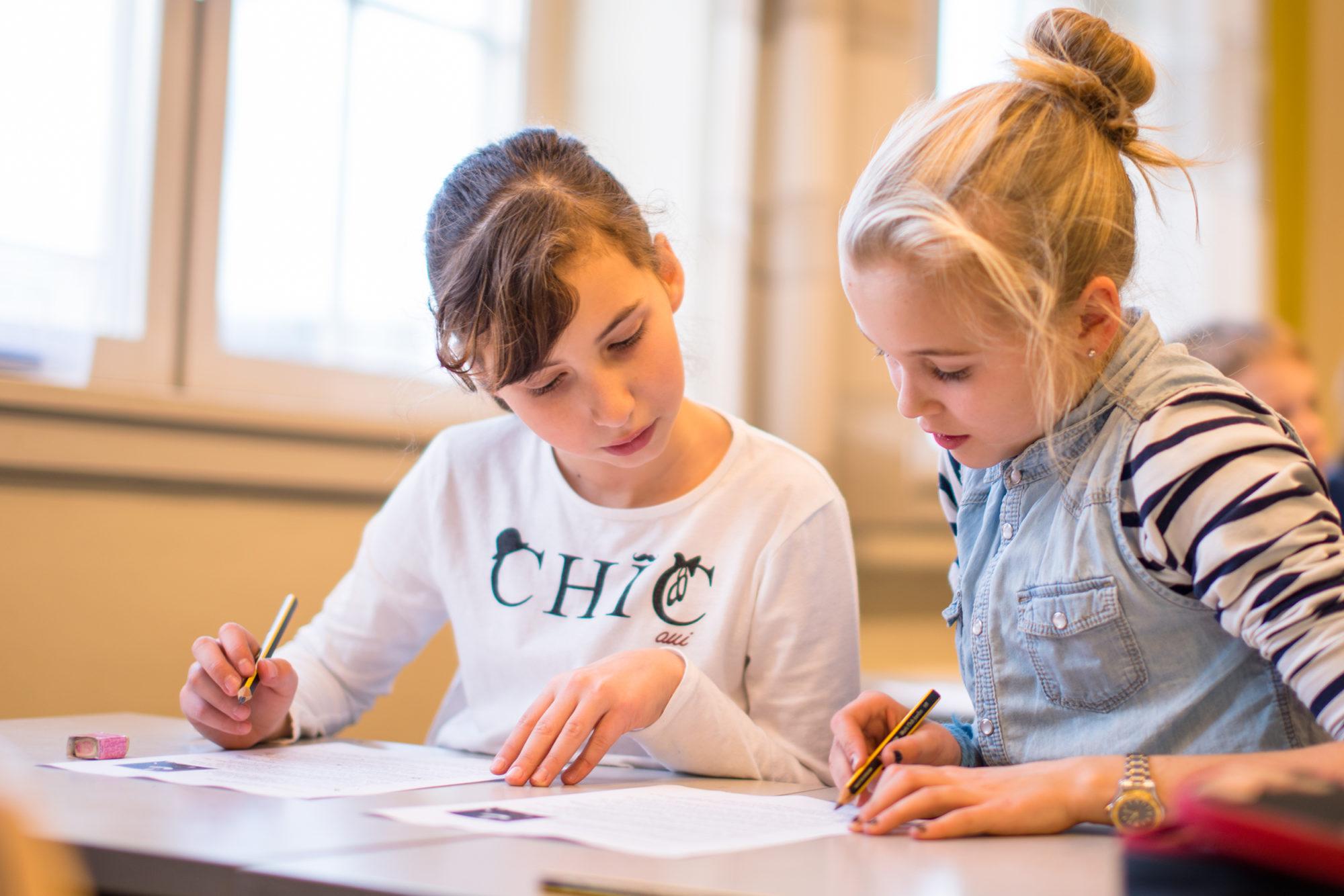 To barneskoleelever som sitter og skriver for hånd