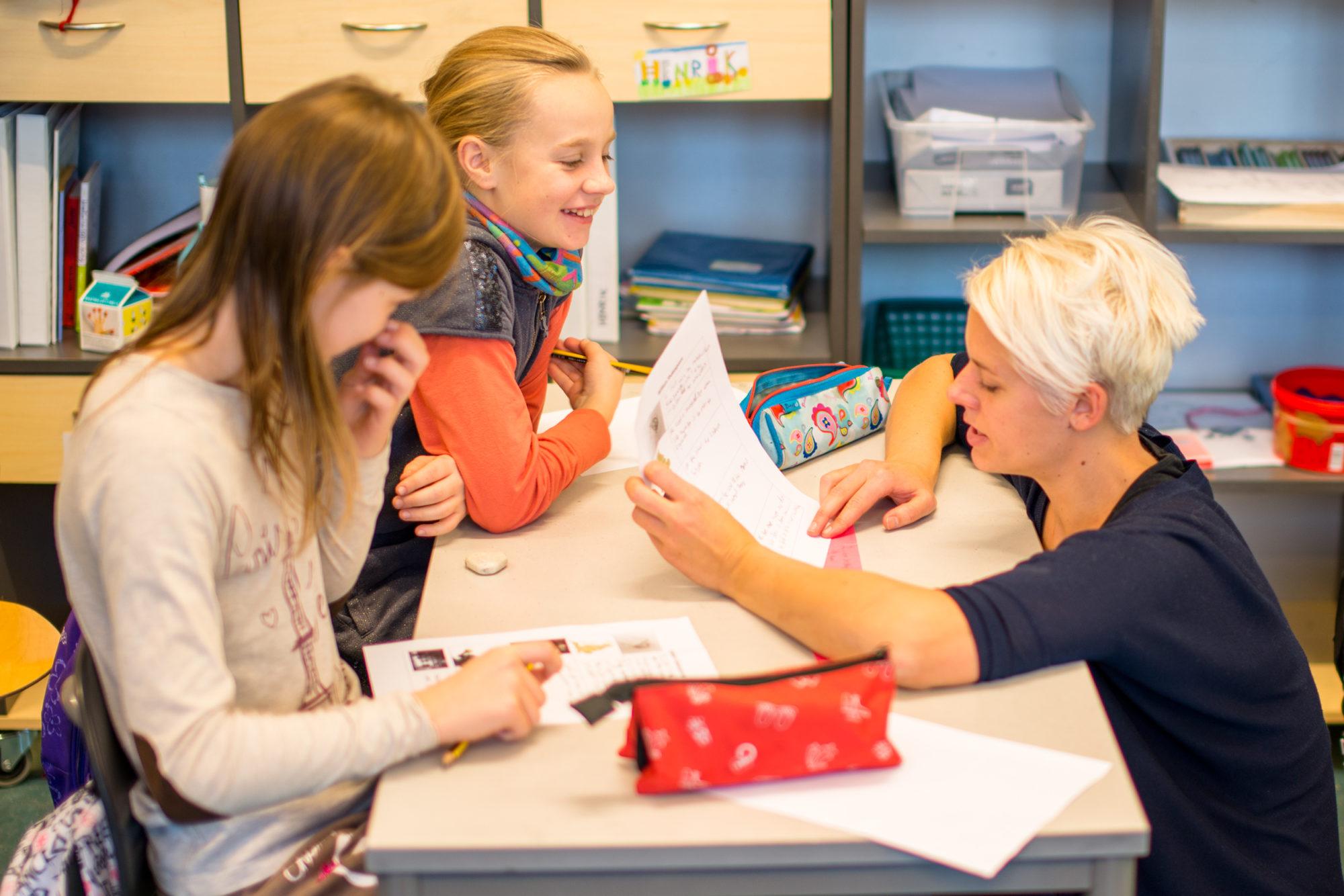 Barneskoleelever får veiledning av lærer