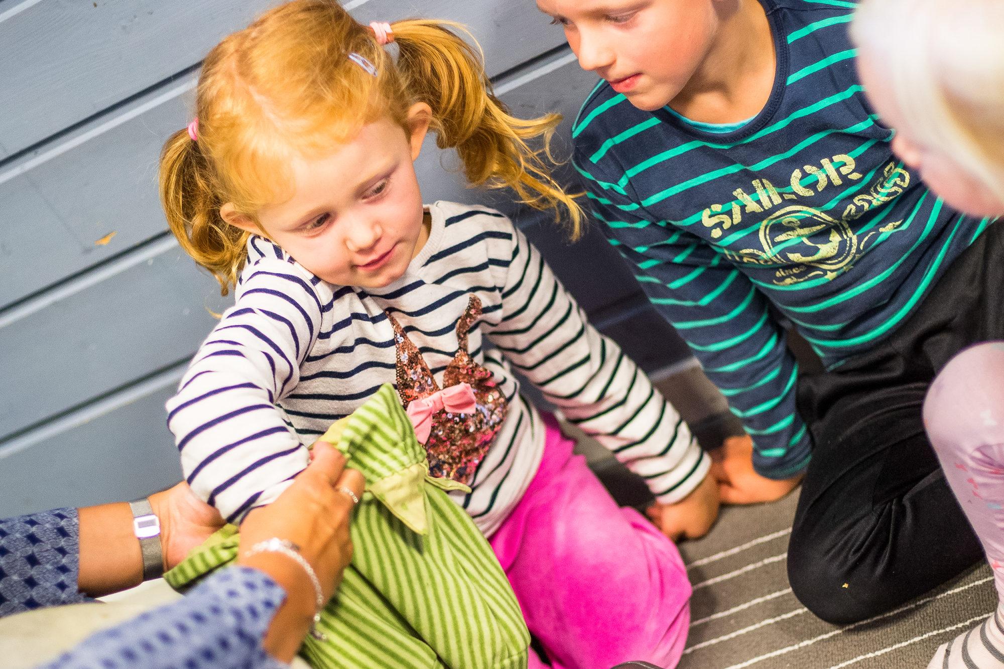 Barnehagejente trekker noe ut av tøyposen