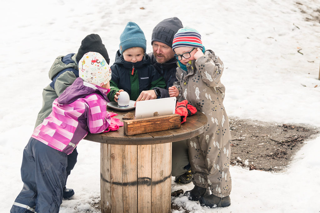 Voksen og barnehagebarn med iPad og teleskop ute om vinteren