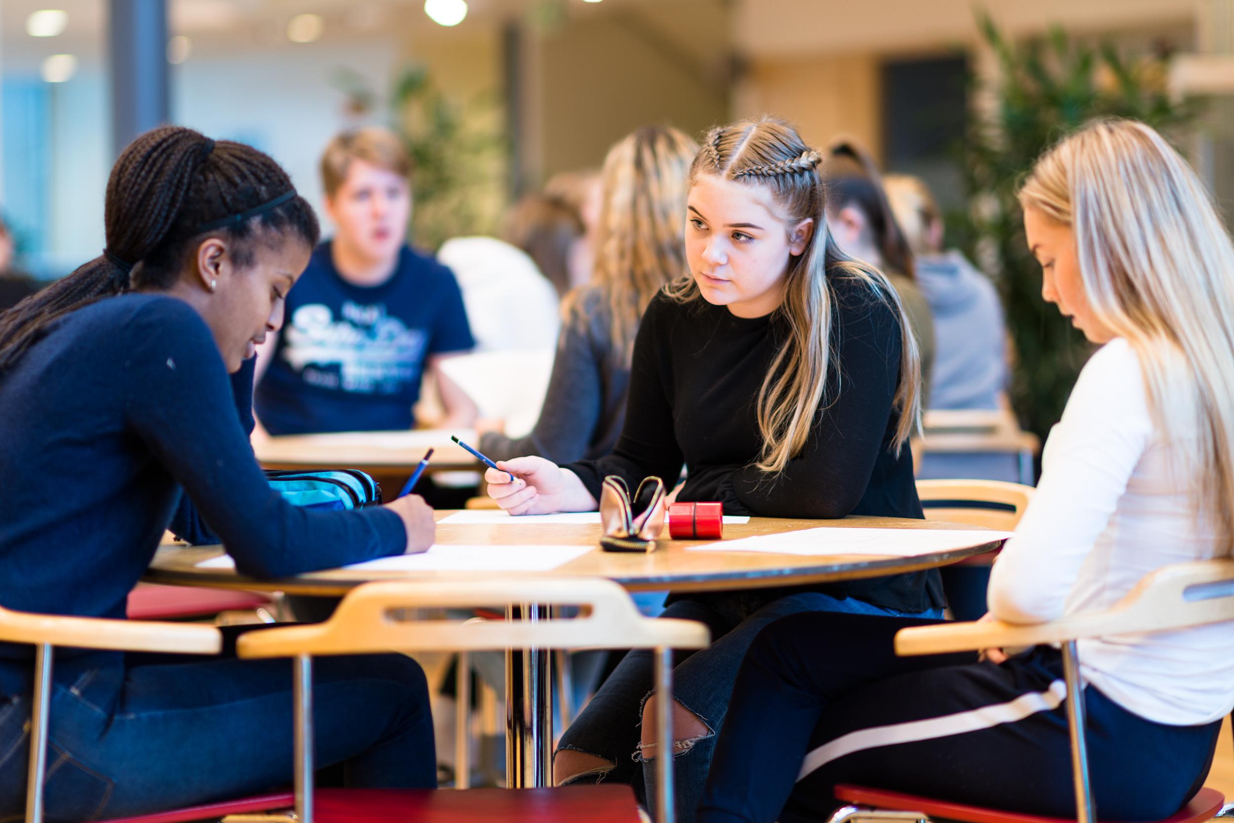 Tre ungdomsskolelever sitter rundt et bord