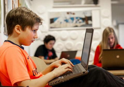 Ungdomsskolegutt jobber på PC