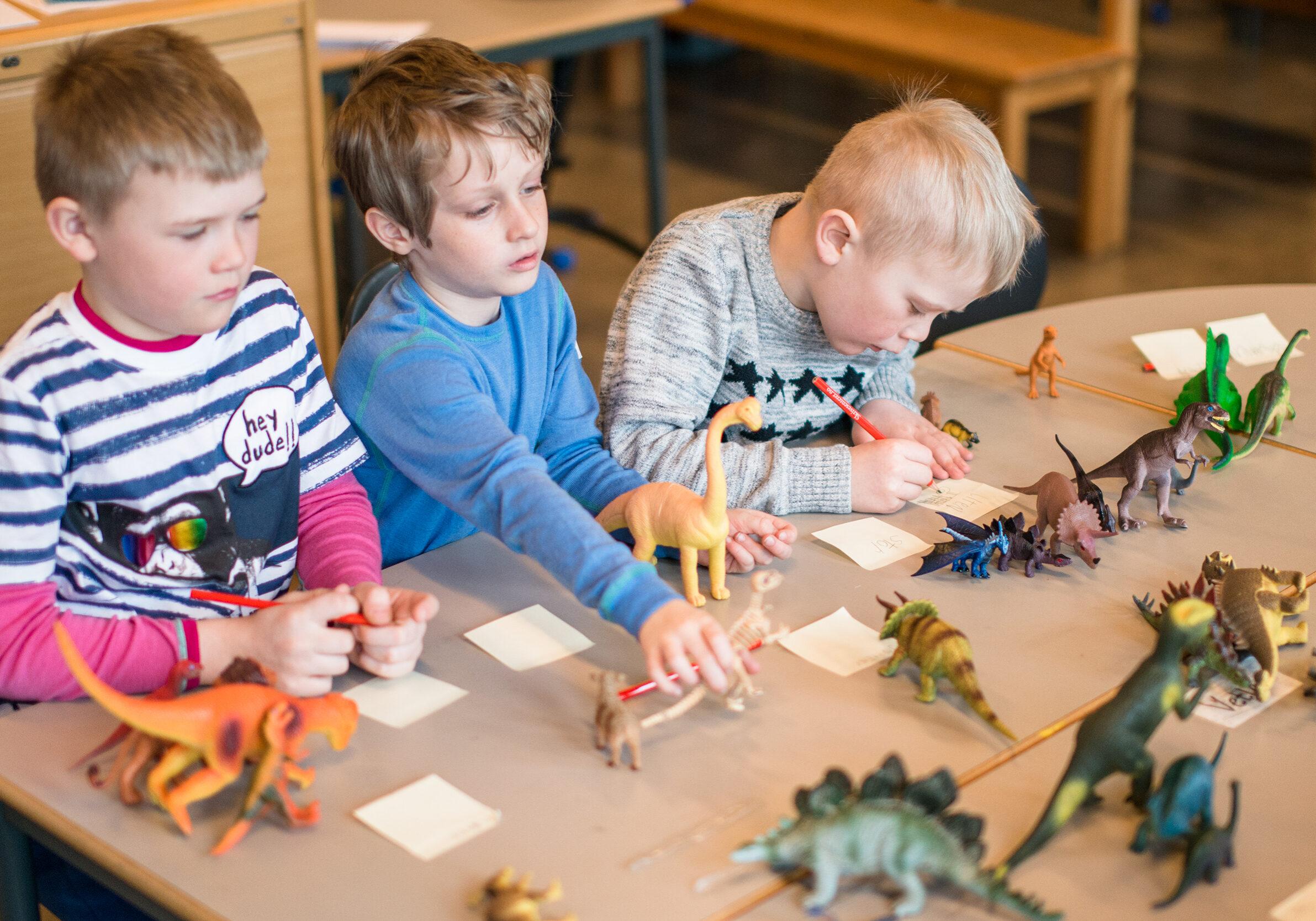 Tre gutter på barnetrinn som skriver om dinosaurer