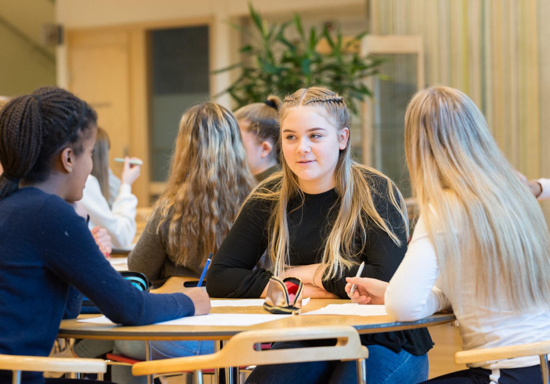 Tre ungdomsskoleelever rundt et bord