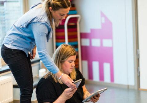 Barnehagepersonal med digitale hjelpemiddel
